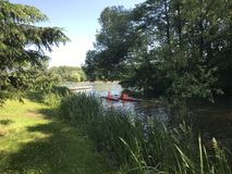 Kayak rowing. Children in lifejackets sail by canoe along the canal in the park. Kayak rowing. Children in lifejackets sail by canoe along the canal in the park stock photo