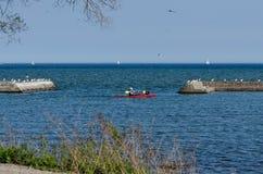 Kayak and sailboats on a lake Royalty Free Stock Images