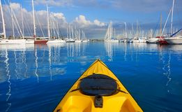 Kayak sailing in a marina port with boats royalty free stock photo