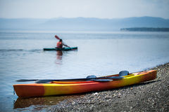 Kayak on the Sea Shore with Kayakers in the Background Royalty Free Stock Images