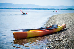 Kayak on the Sea Shore with Kayakers in the Background Royalty Free Stock Photo