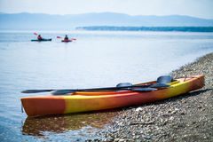 Kayak on the Sea Shore with Kayakers in the Background Royalty Free Stock Photography