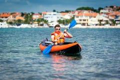Kayak on the sea. Young man paddle a kayak on the sea Stock Photography