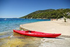 Kayak on the shore of the turquoise sea Stock Images
