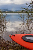 Kayak on shore in willow bushes alongside a lake Stock Photo