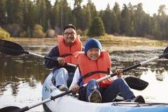 Kayak su un lago rurale, vista frontale del figlio e del padre fotografie stock