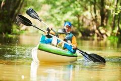 Kayak sul fiume nella famiglia della foresta sulla canoa Ricreazione attiva e vacanza fotografia stock libera da diritti