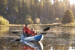 Kayak sul lago rurale, vista frontale del figlio e del padre fotografia stock