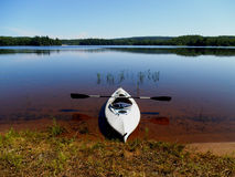Kayak sulla riva di un lago calmo Immagini Stock