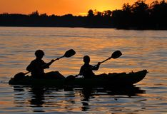 Kayak Sunset. Kayak Paddling Silhouette in Sunset on Lake Stock Images