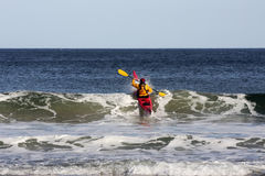Kayak surfant sur la mer Images stock