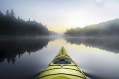 Kayak surfer on a misty lake stock image