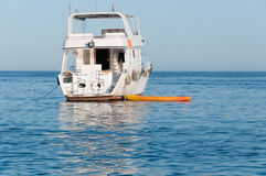 Kayak Tied to a Small Motor Yacht in a Tropical Sea Royalty Free Stock Image