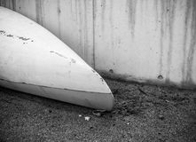 Kayak from white fiberglass plastic with aged marks. With white cord on the beach with black sand with stones on seaside near concrete wall with no people royalty free stock image