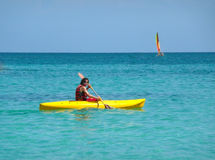 Kayaker. Tanned teenage boy kayaking in a yellow kayak on the ocean on a bright cloudless day. Composition following the rule of thirds with a small catamaran on Stock Images