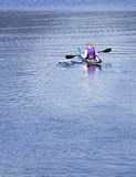 Kayaker barbotant sur le lac Images stock