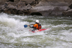 Kayaker battling rapids. And a raging river Stock Photos
