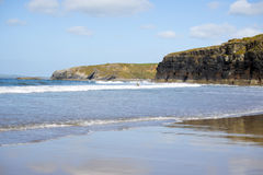 Kayaker breaking waves at ballybunion. Bright winter view of kayaker at ballybunion beach and cliffs on the wild atlantic way in ireland Stock Photography