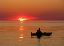 Kayaker on calm water at sunset Stock Images