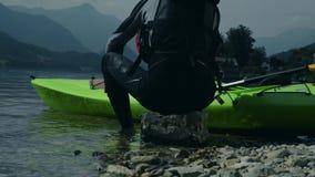 Kayaker che riposa sulla roccia del litorale Sport di kayak stock footage