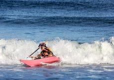 Kayaker combattant la crête d'une vague Image stock