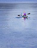 Kayaker die op meer paddelt Stock Afbeeldingen