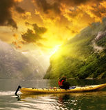 Kayaker eaves Geiranger fjord bay at rainy day in Norway Stock Images