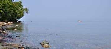 Kayaker en el lago Superior en un día de verano tranquilo Fotos de archivo