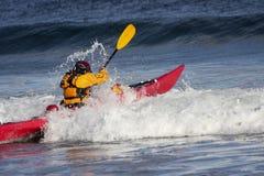 Kayaker en la acción que lucha la onda en el kajak Imagen de archivo