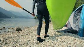 Kayaker en zijn kajak op de meerkust die pret hebben stock video