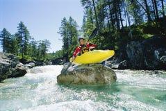 Kayaker encaramado en el canto rodado en el río Foto de archivo