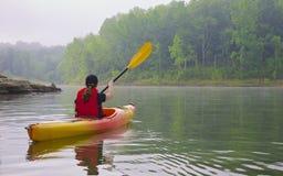 Kayaker féminin sur le lac Photographie stock libre de droits