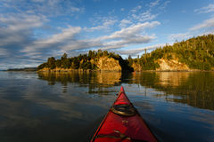 Kayaker heads toward land in remote Alaskan wilderness Stock Photo
