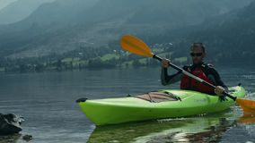 Kayaker on the lake enjoying his vacation stock video