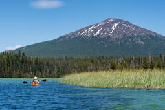Kayaker on mountain lake near Bend, Oregon. A paddler on Oregon`s Hosmer Lake with Mt. Bachelor in the background. The lake is in the Deschutes National Forest royalty free stock photography