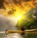 Kayaker okapów Geiranger fjord zatoka przy deszczowym dniem w Norwegia Obrazy Stock