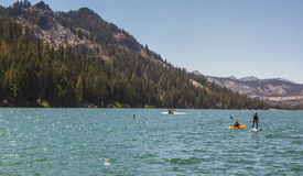 Kayaker and Paddle Boarder on lake in California, USA Royalty Free Stock Images