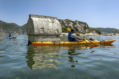 A kayaker paddles past one of the sunken Lycian tombs at the ancient city of Simena in Turkey. Stock Photos