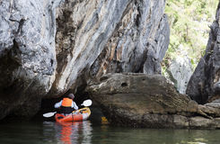 Kayaker Paddling through Caves Stock Photo