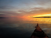 Kayaker pauses to look at glowing Alaskan sunset in remote waters Royalty Free Stock Photography