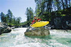 Kayaker perched on boulder in river Stock Photo