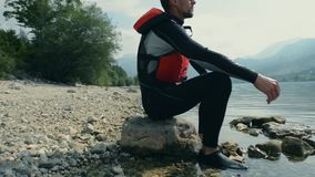 Kayaker resting on the rocky lake shore stock video footage