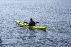 Kayaker seul barbotant dans un kayak par l'aviron de mer, le sport aquatique actif et les loisirs, kayaking Image stock