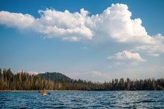 Kayaker sous de grands nuages gonflés images stock