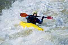 Kayaker training. The unidentified sportsman on a yellow kayak balances, trying to be kept in a rough threshold of the river. Photo taken on: April 11, 2009 Royalty Free Stock Photography