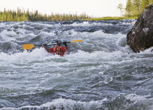 Kayaker turning over in whitewater Stock Image