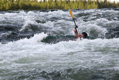 Kayaker turning over in whitewater Stock Photos
