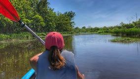 Kayakeren paddlar till och med vatten av deltan arkivfoton