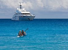 Kayakers στο καγιάκ και ένα όμορφο γιοτ στο υπόβαθρο των σύννεφων στο νησί Kefalonia στην ιόνια θάλασσα στην Ελλάδα στοκ εικόνα