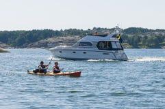 2 kayakers близко к flybridgeboat Стоковые Фото